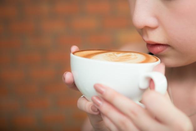 Mooie aziatische gril het drinken koffie in koffierestaurant Premium Foto
