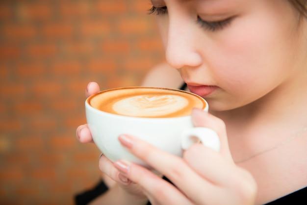Mooie aziatische gril het drinken koffie in koffierestaurant