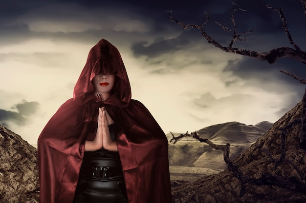 Mooie aziatische heksenvrouw met het rode mantel bidden