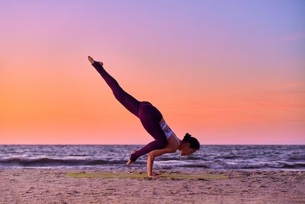 Mooie aziatische jonge vrouw beoefent yoga asana eka pada bakasana - een been kraan pose asana yoga pose.