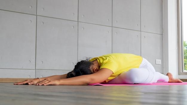 Mooie aziatische jonge vrouw die sportkleding het praktizeren yoga in studio, natuurlijk licht draagt. concept: yoga stelt voor beginner.