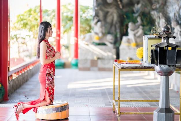 Mooie aziatische jonge vrouw dragen rode traditionele chinese cheongsam, zittend voor bidden tot boeddhabeeld voor chinees nieuwjaar festival op chinees heiligdom