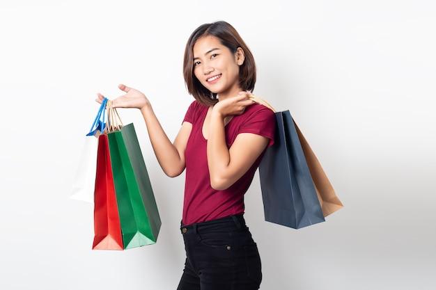 Mooie aziatische jonge vrouw glimlachend bedrijf boodschappentassen geïsoleerd