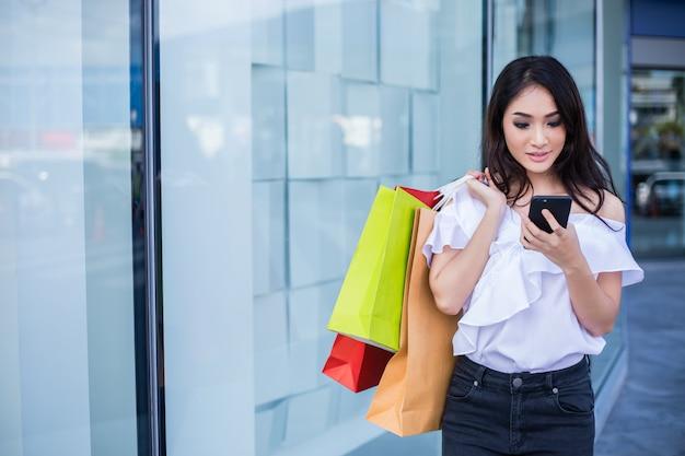 Mooie aziatische jonge vrouw met boodschappentassen met behulp van haar slimme telefoon met glimlach terwijl je op de kledingwinkel. geluk, consumentisme, verkoop en mensen concept