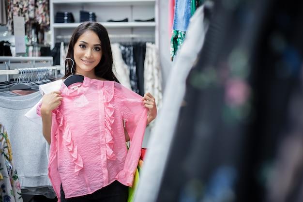 Mooie aziatische jonge vrouw met boodschappentassen met glimlach terwijl je bij de kledingwinkel. geluk, consumentisme, verkoop en mensen concept