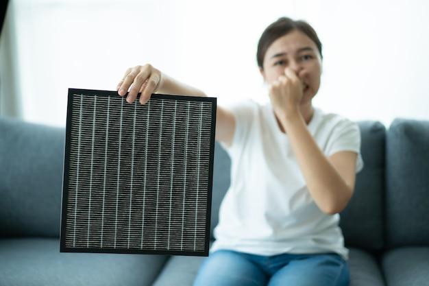 Mooie aziatische jonge vrouw met een hepa-koolstofluchtzuiveringsfilter in de woonkamer, vrouw bereidt een luchtzuiveringsfilter voor om de oude te vervangen. gezondheidszorg en goed leven levensstijl concept.