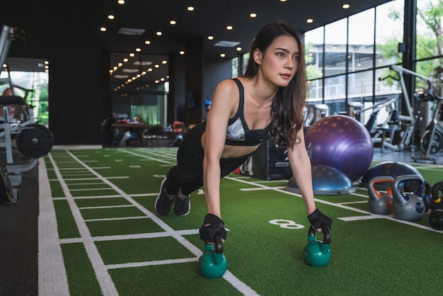 Mooie aziatische jonge vrouwentraining opleiding en oefening met kettlebellgewicht bij fitness de sportclub van de gymnastieksport