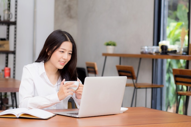 Mooie aziatische jonge zakenvrouw opgewonden en blij van het succes met de laptop.