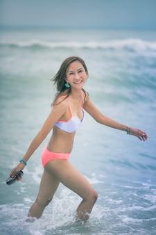 Mooie aziatische jongere vrouw die bikini op overzees strand met het glimlachen gezicht draagt