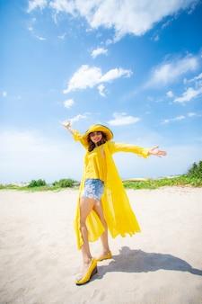 Mooie aziatische jongere vrouw die het gele kleding ontspannen op het strand van de zomervaitaiton dragen