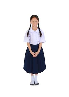 Mooie aziatische meisje kind in thaise schooluniform staande geïsoleerd op een witte achtergrond. afbeelding volledige lengte met uitknippad