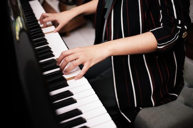 Mooie aziatische meisje leren piano spelen.