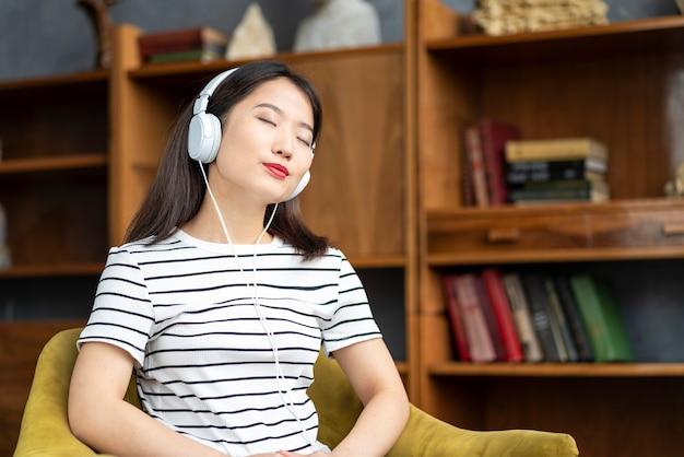 Mooie aziatische meisje, luisteren naar muziek met een koptelefoon zittend in een stoel