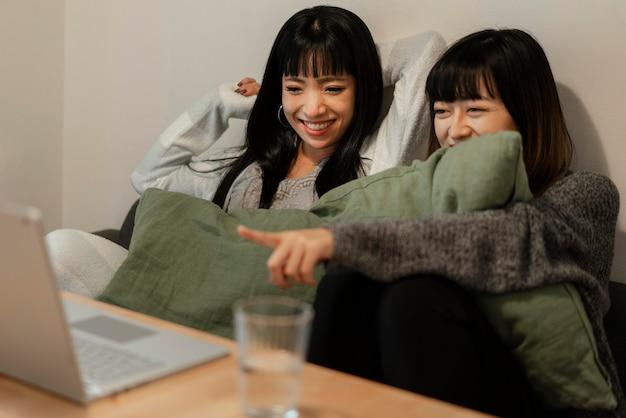 Mooie aziatische meisjes die samen een film kijken