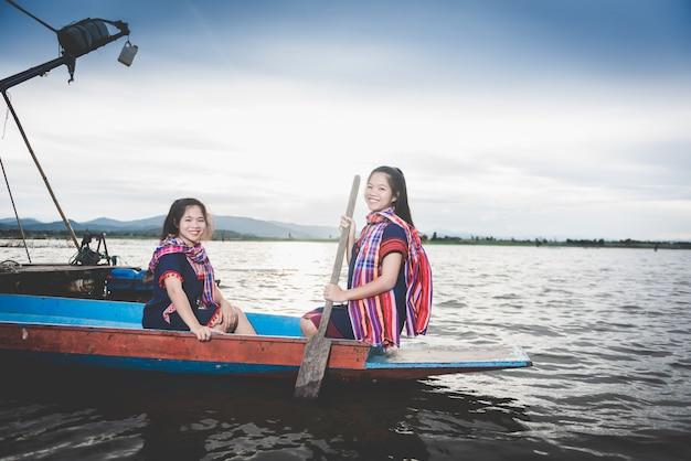 Mooie aziatische meisjes op vissersboot in meer om vissen bij platteland van thailand te vangen