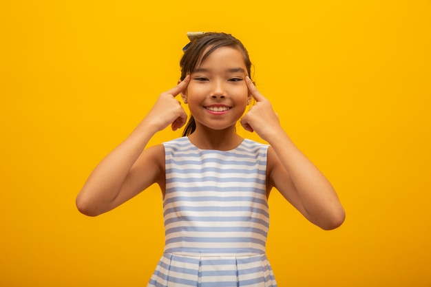 Mooie aziatische meisjeszitting op gele achtergrond