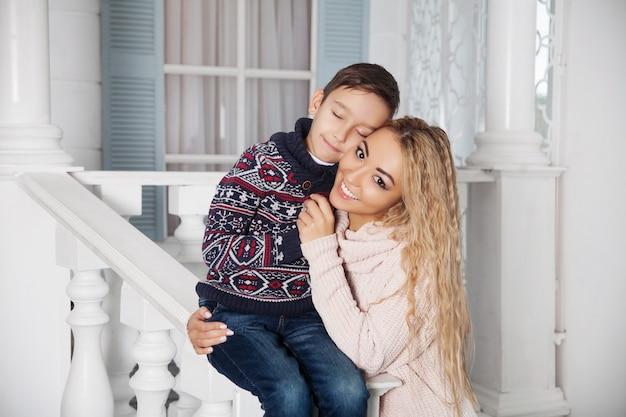 Mooie aziatische moeder die met haar kleine zoon op de witte voorportiek van een vakantiehuis van het land koestert.
