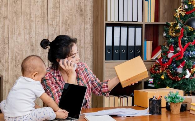Mooie aziatische moeder met baby die thuis gebruikend laptop dichtbij de kerstboom werkt