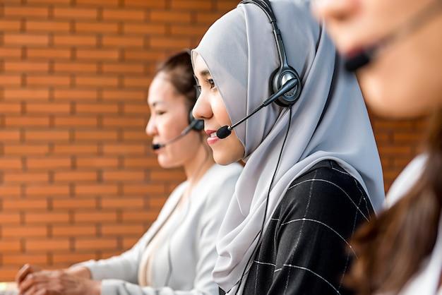 Mooie aziatische moslimvrouw die in call centre met haar team werkt