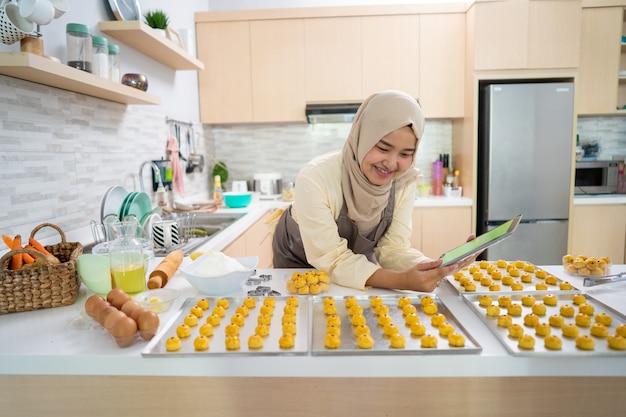 Mooie aziatische moslimvrouw die thuis nastarcake maakt voor eid mubarak