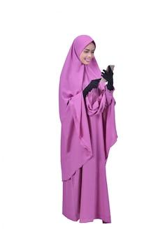 Mooie aziatische moslimvrouw die zich terwijl het gebruiken van mobiele telefoon bevindt