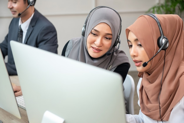 Mooie aziatische moslimvrouwen die in call centrebureau werken