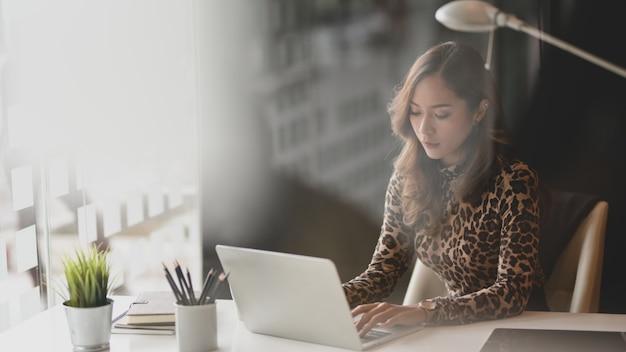 Mooie aziatische onderneemster die aan haar project werkt terwijl het typen op laptop computer