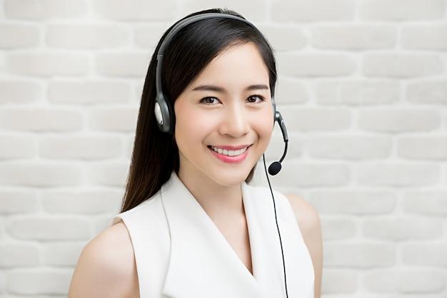 Mooie aziatische onderneemster die microfoonhoofdtelefoon draagt als agent van de telemarketing klantendienst