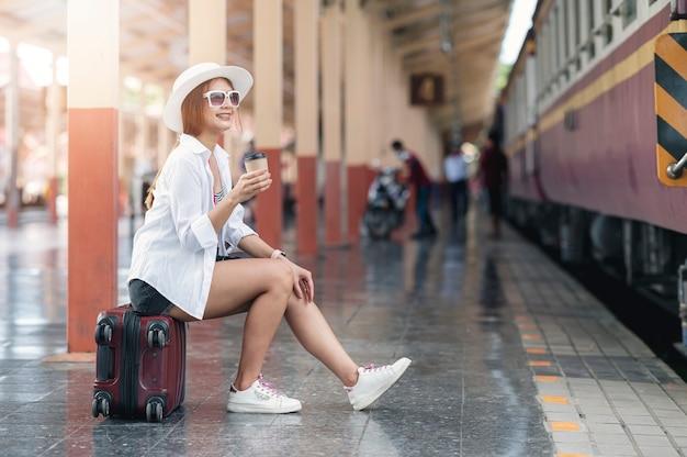 Mooie aziatische reiziger met hoed en bril met een kopje koffie terwijl hij op bagage op het treinstation zit, wachtend op vertrek