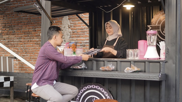 Mooie aziatische serveerster die een menulijst geeft aan klanten bij de angkringan-containerstand