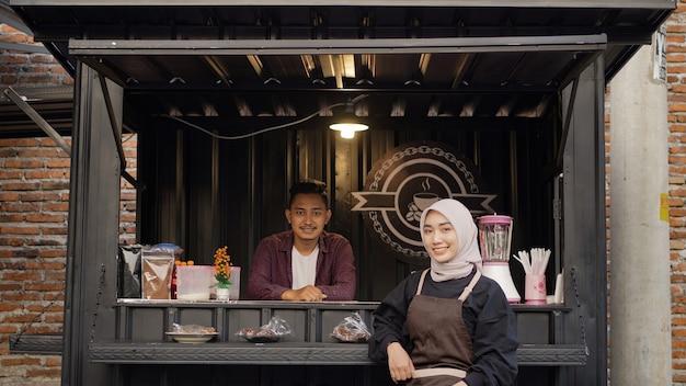 Mooie aziatische serveerster en coole knappe kerel bij de angkringan-containercabine?