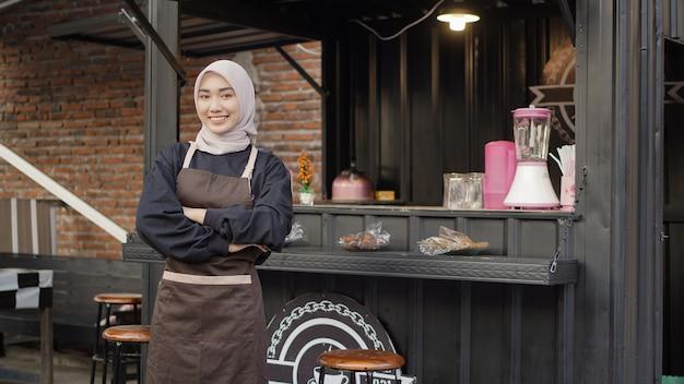 Mooie aziatische serveerster met armen klaar om te serveren in de container van de cafécabine