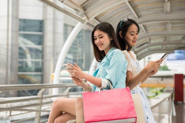 Mooie aziatische shopaholic-vrienden breken met winkelen en gebruiken een smartphone om te chatten of sociale media te spelen in de moderne stad van bangkok met veel koopmanstassen. glimlachende jonge vrouwen in een gelukkig gevoel.