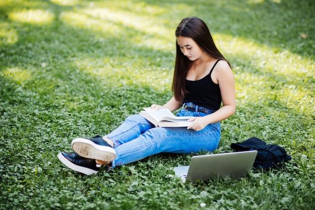 Mooie aziatische student die verslagen in document notitieboekje houden terwijl online het bestuderen met laptop, zittend op gras, openlucht