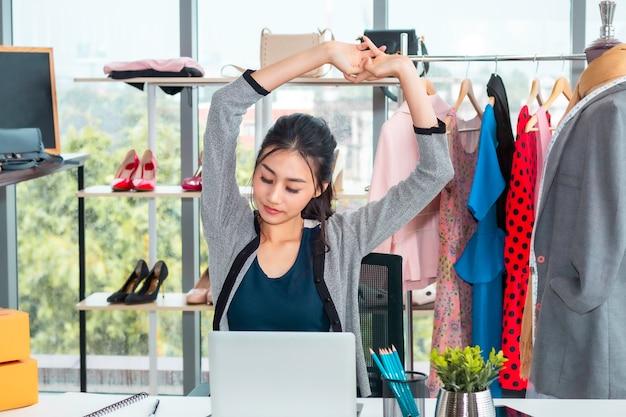 Mooie aziatische toevallige vrouw die tijdens werkende start kleine bedrijfsondernemer kmo in klerenwinkel wordt vermoeid.