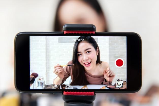 Mooie aziatische vlogger van de vrouwenschoonheid de video van de make-uptutorial door smartphone