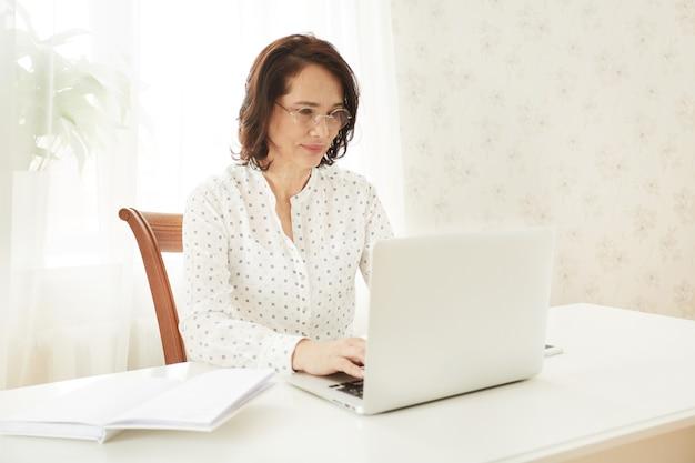 Mooie aziatische volwassen vrouw met behulp van draagbare laptopcomputer