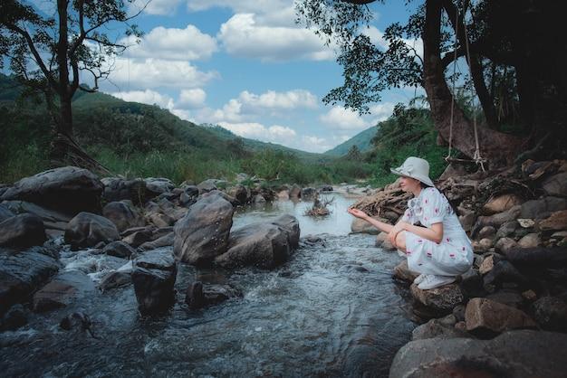 Mooie aziatische vrouw aan de rivier