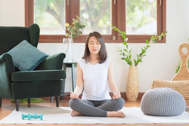 Mooie aziatische vrouw blijf kalm en mediteert tijdens het beoefenen van yoga thuis voor een gezonde levensstijl