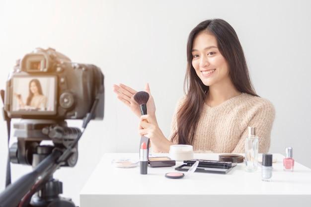 Mooie aziatische vrouw blogger laat zien hoe make-up en cosmetica te gebruiken.