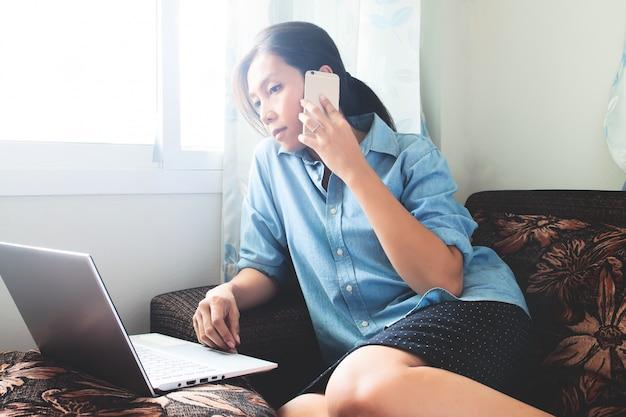 Mooie aziatische vrouw die aan laptop thuis werkt.