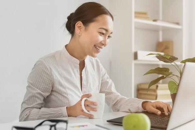 Mooie aziatische vrouw die aan laptop werkt