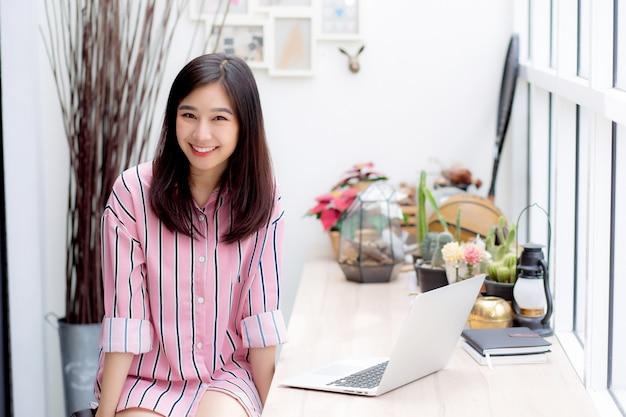 Mooie aziatische vrouw die aan laptopzitting bij koffiewinkel werkt