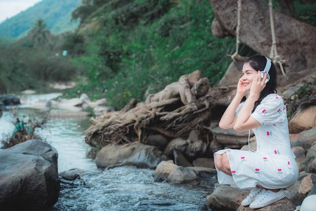 Mooie aziatische vrouw die aan muziek bij de rivier luistert