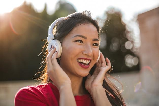 Mooie aziatische vrouw die aan muziek luistert