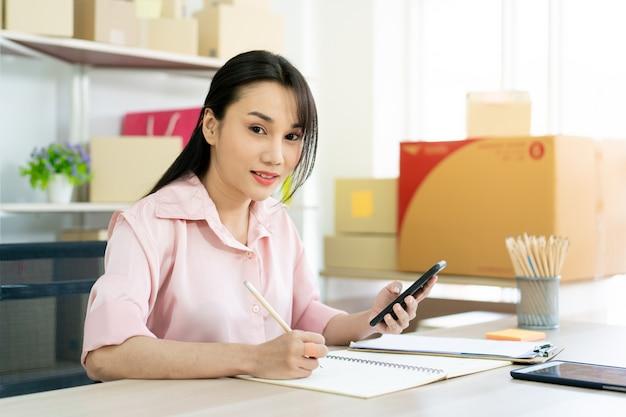Mooie aziatische vrouw die berekeningen doet