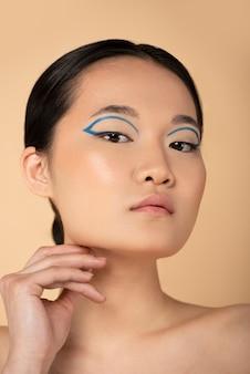 Mooie aziatische vrouw die blauwe eyeliner draagt