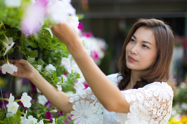 Mooie aziatische vrouw die bloem in bloemenwinkel selecteert, levensstijl van moderne huisvrouw.