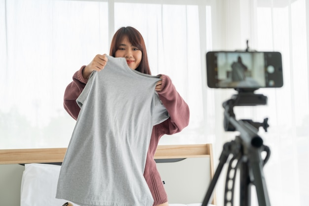 Mooie aziatische vrouw die blogger kleren op camera tonen aan het opnemen van vlog video
