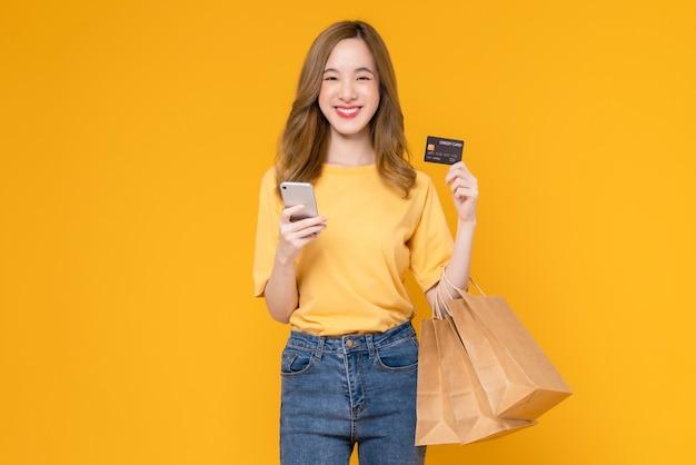 Mooie aziatische vrouw die bruine blanco ambachtelijke papieren boodschappentassen vasthoudt en creditcard op gele achtergrond toont.